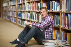 Happy student sitting on library floor reading. In college Royalty Free Stock Image