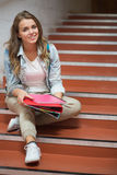 Happy student sitting on stairs looking at camera Stock Images