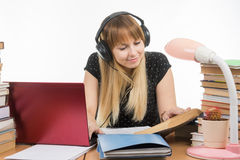 Happy student sitting at table and preparing for exams in headphones Royalty Free Stock Photo