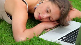 Happy student sleeping on grass in front of laptop stock video