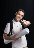 Happy student. A happy student.He smiles us.He weared a white t-shirt. He keeps a book and architectural sheet of paper.He has a bag behind.His smile shows us Stock Photography