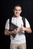 Happy student. A happy student. he smiles us. he weared a white t-shirt.He keeps a book and has a bag behind. his smile shows us his positive mood and happiness Royalty Free Stock Image