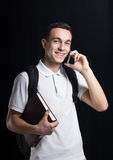 Happy student. A happy student.He smiles us.He weared a white t-shirt. He keeps a book and mobile phone.He has a bag behind.His smile shows us his positive mood Royalty Free Stock Photo