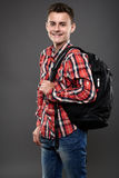 Happy student. Happy and smiling teenager student with backpack on gray background Stock Photos