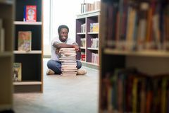 Happy Student With Stacked Books Sitting In Royalty Free Stock Photos
