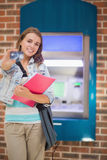 Happy student standing showing her card to camera at the atm Stock Image