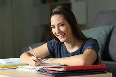 Happy student studying late hours looking at you. Happy student studying late hours in the night looking at you at home Royalty Free Stock Photography