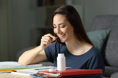 Student studying taking a vitamin pill. Happy student studying late hours in the night taking a vitamin pill at home Royalty Free Stock Images