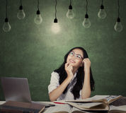 Happy student studying under lightbulb Royalty Free Stock Photos