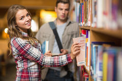 Happy student taking book from shelf in library Royalty Free Stock Photography