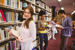 Happy student taking book from shelf Royalty Free Stock Photography