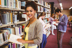 Happy student taking book from shelf Stock Photo