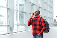 Happy student talking on mobile phone at rail station. Portrait of happy young african student talking on mobile phone at rail station Royalty Free Stock Image