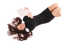 Happy student teenage girl lying on the floor looking at tablet Stock Image