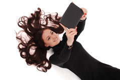 Happy student teenage girl lying on the floor looking at tablet Royalty Free Stock Photos