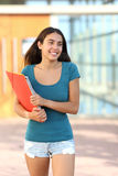 Happy student teenager girl walking out of the school. With the building in the background stock photography