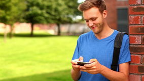 Happy student texting on his phone outside stock video footage