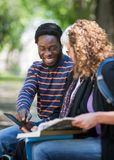 Happy Student Using Digital Tablet With Friends On. Happy African American university student using digital tablet with friends on campus Royalty Free Stock Images