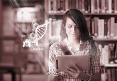 Happy student using futuristic interface to learn about science from digital tablet. In college library Stock Images