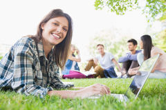 Happy student using her laptop outside Stock Image