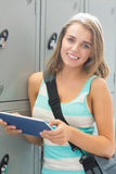 Happy student using her tablet beside lockers looking at camera Royalty Free Stock Photography