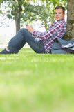 Happy student using his tablet to study outside. On college campus Stock Photography