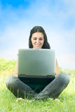 Happy student using laptop. At the park Stock Images