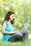 Happy student using laptop. At the park Stock Image