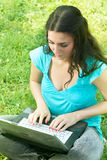 Happy student using laptop. At the park Stock Photo