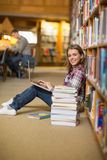 Happy student using laptop on library floor looking at laptop Royalty Free Stock Image