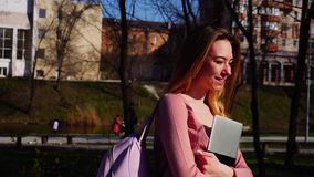 Happy student walking in park with laptop and backpack in slow motion. Gladden student passing in slow motion with laptop and backpack. Concept of having break stock video footage