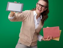 Happy student woman with books showing tablet PC blank screen. Happy young student woman with books showing tablet PC blank screen against green background royalty free stock photo