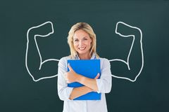 Happy student woman with fists graphic standing against green blackboard Stock Image