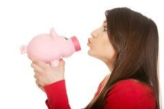 Young woman kissing a piggybank. stock photo