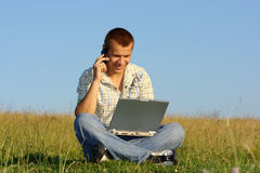 Happy student working with laptop on green meadow Royalty Free Stock Image