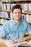 Happy student writing to notebook in library Stock Photo