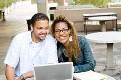 Happy students. Two happy african university students study computer laptop together outdoors Stock Photos