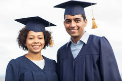 Happy students or bachelors in mortar boards Royalty Free Stock Image