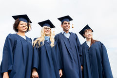 Happy students or bachelors in mortarboards Royalty Free Stock Photos