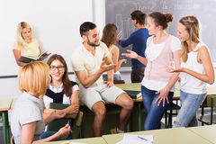 Happy students during break in classroom. Happy adult students talking during break in classroom Royalty Free Stock Photo