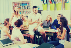 Happy students during break in classroom. Happy young students during break in classroom Royalty Free Stock Photography