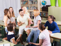 Happy students during break in classroom. Happy young students during break in classroom interior Stock Photo