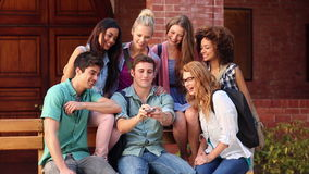 Happy students chatting together outside and taking a photo Royalty Free Stock Photos
