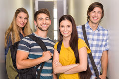 Happy students at college corridor. Portrait of happy students standing at college corridor Stock Photo