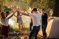 Happy students are dancing around the bonfire stock photography