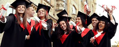 Students with diplomas near campus. Banner design. Happy students with diplomas near campus. Banner design