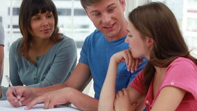 Happy students doing their homework together stock footage