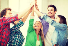 Happy students giving high five at school. Education and friendship concept - happy students giving high five at school Royalty Free Stock Photos