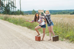 Happy students hitchhike with cardboard on road Stock Images