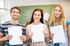 Happy students holding papers in class Stock Photography